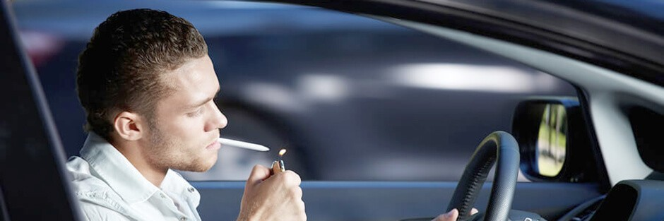 A young man is driving while lighting up a joint to smoke marijuana
