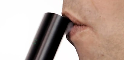 Profile of a male taking a drag from pax vaporizer with vapor showing