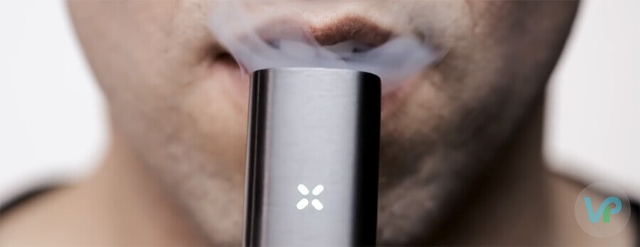 A male taking a drag from Pax vaporizer while smoke is showing