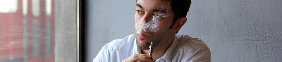 Young man is smoking a marijuana vaporizer pen
