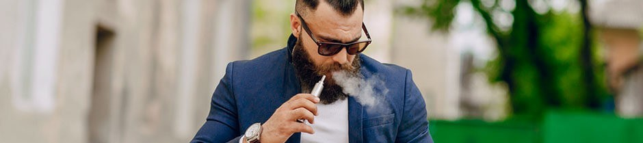 Bearded man is holding a weed vaporizer pen