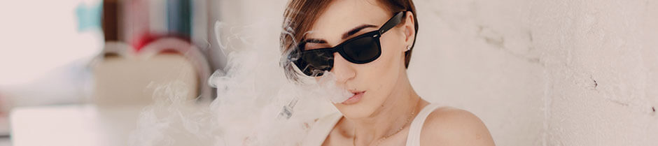 A pretty lady with dark glasses is exhaling vapor while holding a marijuana vape pen